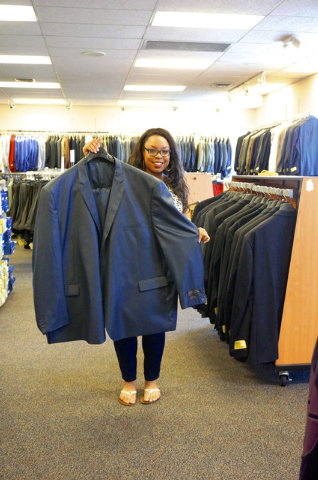 Mastroianni Fashions sales associate Natalie Tippett displays a suit at the 1701 S. Decatur Blvd. store, which includes a Big & Tall component. (Diane Taylor/Special to View)