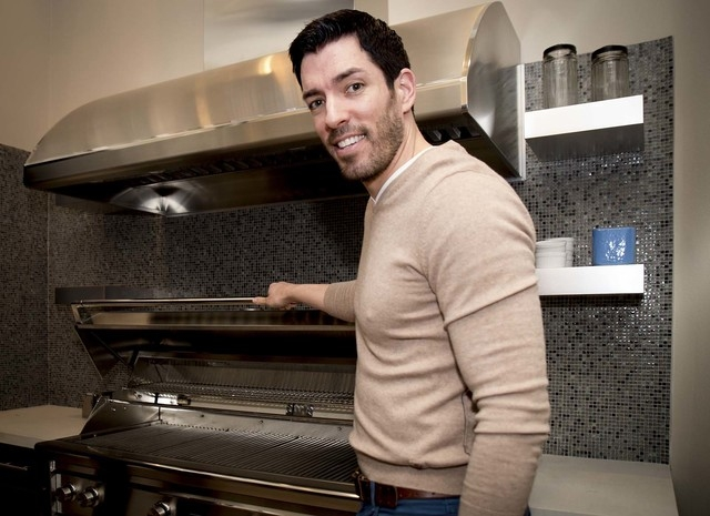 Drew Scott shows of a grill large enough to hold 35 steaks. (Tonya Harvey/Real Estate Millions)