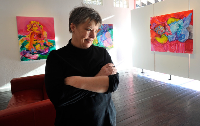 Marty Walsh watches her husband, Pete, work at the Trifecta Gallery on Dec. 23. After 11 years, the couple are closing their gallery at The Arts Factory and moving to Ireland. (David Becker/View)