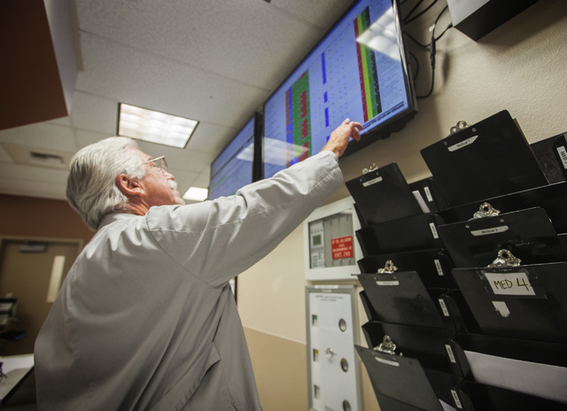 Dr. Dale Carrison monitors a hospital status board in the University Medical Center emergency department  on  Wednesday, Jan.14, 2015. Flu-like symptoms have force several hospitals in the valley  ...