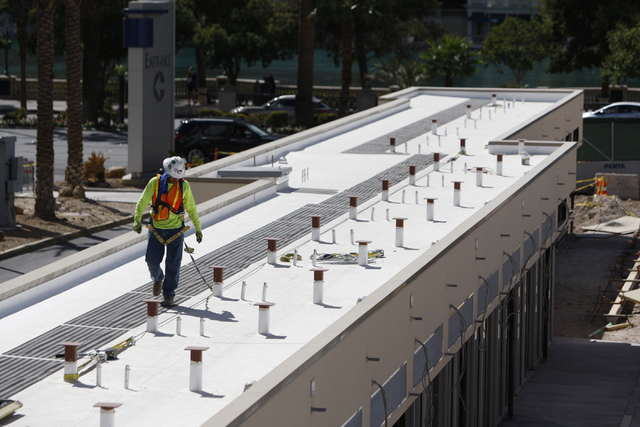 A construction worker stands of the roof of a building at the construction site of the future Grand Bazaar Shops at Bally's casino-hotel in Las Vegas during a tour Thursday, Sept. 4, 2014. Michael ...