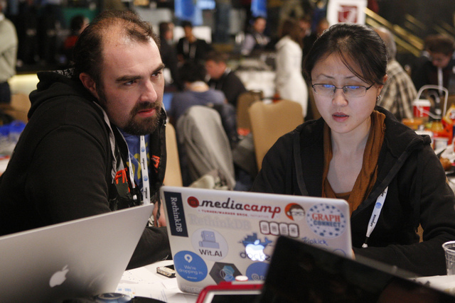 Matthew Young, left, and Serena Xu, members of the Personal Black Box team, work at their station during the 2015 AT&T Hackathon competition at the Palms casino-hotel in Las Vegas Sunday, Jan. 4,  ...