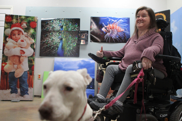 Kelly McMahon, director of the Hearts Alive Village Las Vegas, holds her therapy dog Peewee, a 12-years-old pit bull, as she speaks about their program at Pictographics, 4830 W. Oquendo Road, in L ...