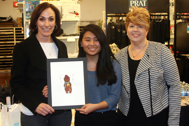 Kaitlyn Ramos, center, an 11th-grader at Liberty High School, holds her artwork Dec. 10 that won first place in The Public Education Foundation's annual holiday card contest. Shari Scheele, left ...
