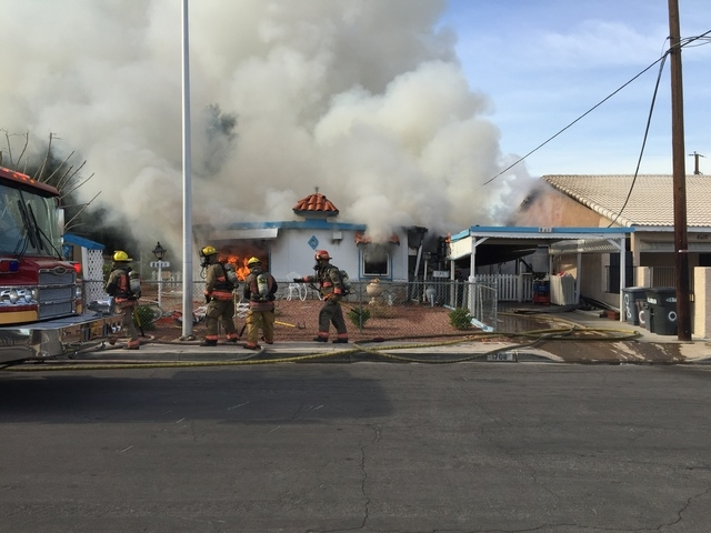 Las Vegas firefighters are seen battling a house fire at 1708 Pacific St., near the intersection of Oakey Boulevard and Eastern Avenue on Monday, Jan. 5, 2015. A person was rescued from the burnin ...