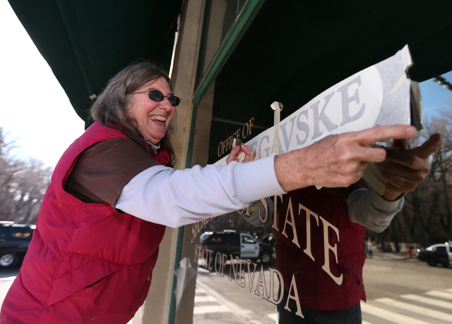 Mary Lou (who declined to give her last name), with Alpine Signs, installs new signs at the Secretary of State's office, in Carson City, Nev., on Monday, Jan. 5, 2015. Secretary of State Barbara C ...