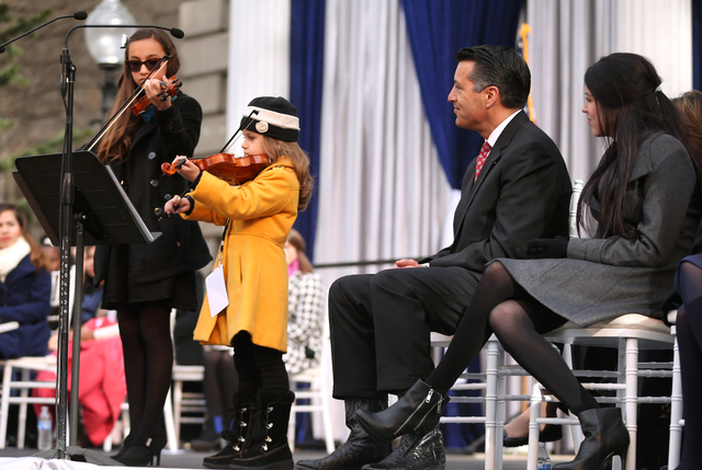 "Gov. Brian Sandoval and his daughter Maddy, right, listen to a performance of ""Home Means Nevada"" by Alexia Ciobanu, 7, and Haylee Reynolds, 13, during the inauguration on the steps of t ..."