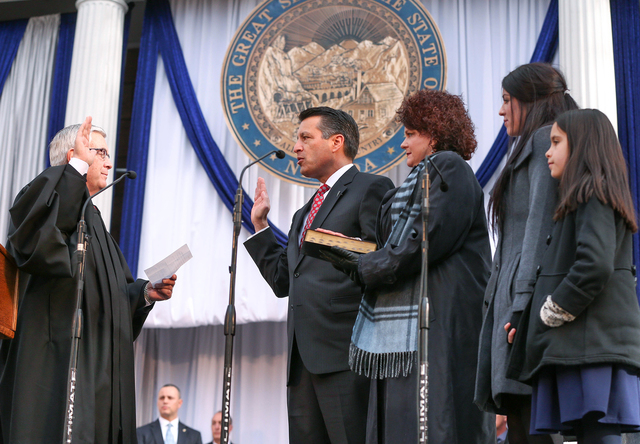 Nevada Gov. Brian Sandoval takes the oath of office from Supreme Court Chief Justice James Hardesty on the steps of the Capitol, in Carson City, Nev., on Monday, Jan. 5, 2015. First lady Kathleen  ...