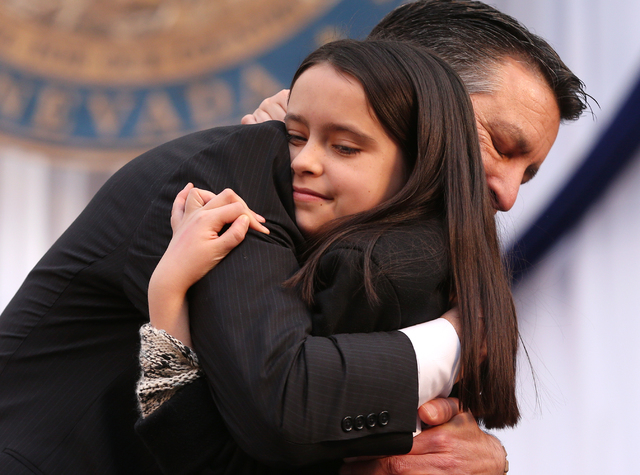 Gov. Brian Sandoval hugs his daughter Marisa, 10, after taking the oath of office on the steps of the Capitol, in Carson City, Nev., on Monday, Jan. 5, 2015. (Las Vegas Review-Journal/Cathleen All ...
