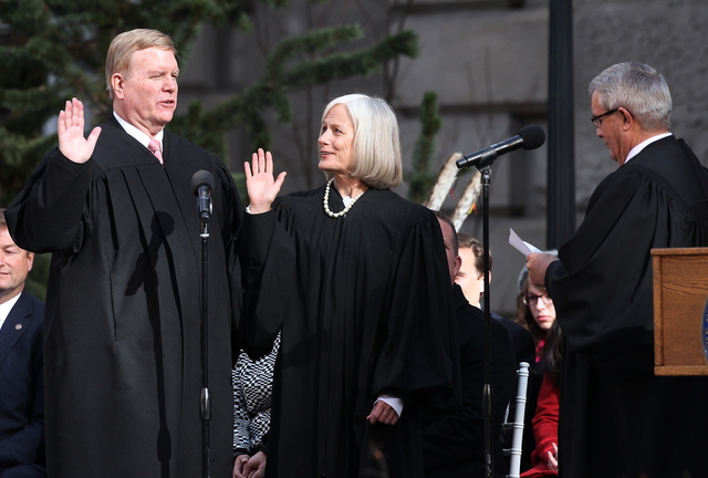 Supreme Court Justices Mark Gibbons and Kristina Pickering take the oath of office from Chief Justice James Hardesty during the inaugural ceremony on the steps of the Capitol, in Carson City, Nev. ...
