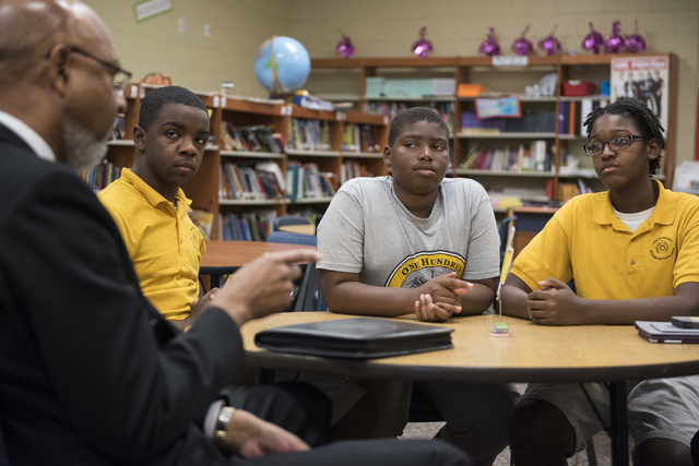 President of the mentorship program of 100 Black Men, Joe  Jones, left, speaks to Tre'Jon Hawkins, 13, Sir Mells, 11, and Kevin Carroll, 14, at 100 Academy of Excellence charter school. (Martin S. ...