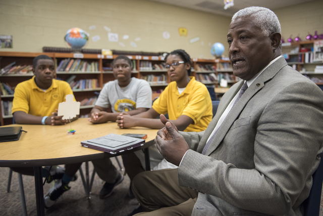 Vice president of external affairs for the mentorship program of 100 Black Men, Leroy Wordlaw, right, discusses the program at 100 Academy of Excellence charter school. Looking on are students in  ...