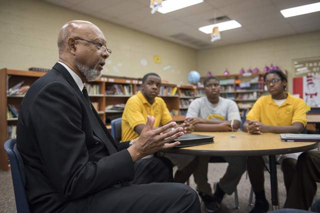 President of the 100 Black Men mentorship program, Joe  Jones, left, discusses the program at 100 Academy of Excellence charter school. Looking on are students in the program, from second from lef ...