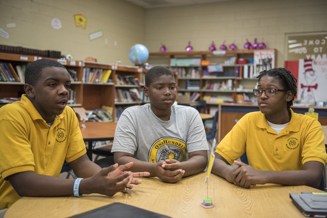 "Students from the 100 Academy of Excellence charter school from left, Tre'Jon Hawkins, 13, Sir Mells, 11, and Kevin Carroll, 14, speak about being mentored by members if ""100 Black Men"" at their s ..."