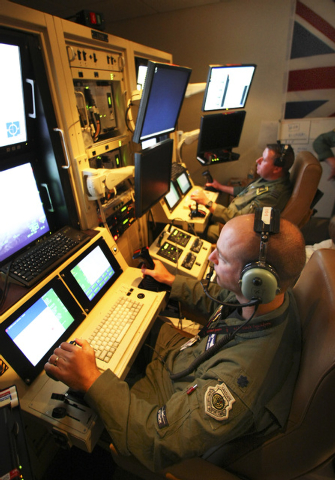 U.S. Air Force Lt. Col. Jon Greene, left, and Royal Air Force Wing Commander Andy Jeffrey operate a MQ-9 Reaper unmanned aerial vehicle that are flying a mission 10,000 miles away in Afghanistan v ...