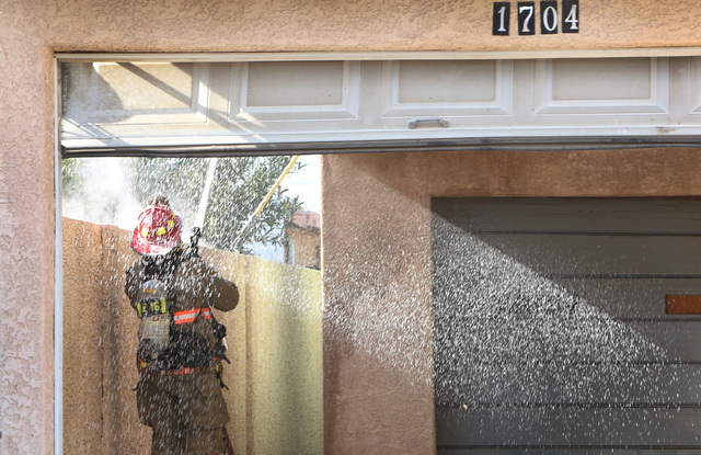 A Las Vegas firefighter is seen battling a house fire at 1708 Pacific St., near the intersection of Oakey Boulevard and Eastern Avenue on Monday, Jan. 5, 2015. A person was rescued from the burnin ...