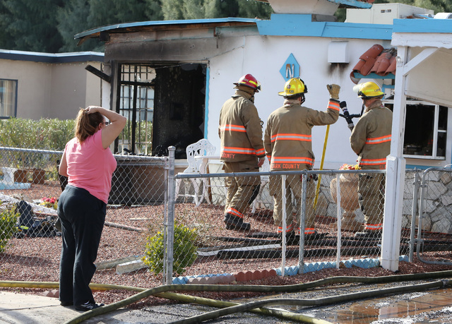 A woman, left, reacts to the fire damage to her home at 1708 Pacific St., near the intersection of Oakey Boulevard and Eastern Avenue on Monday, Jan. 5, 2015. A person was rescued from the burning ...
