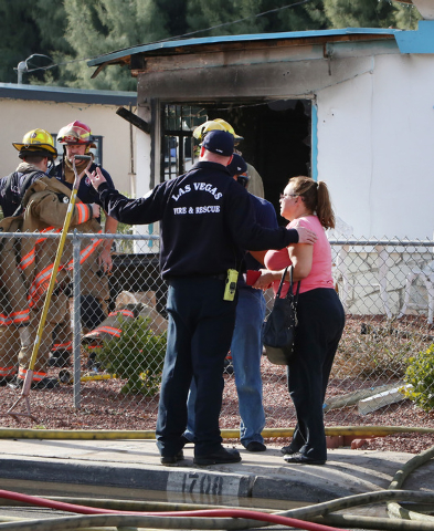 A woman, right, whose home was damaged in a fire is escorted by fire officials after surveying the damage at 1708 Pacific St., near the intersection of Oakey Boulevard and Eastern Avenue on Monday ...