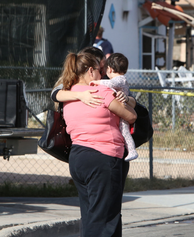 A woman, holding a toddler, whose home was damaged in a fire is comforted by her daughter near her house at 1708 Pacific St., near the intersection of Oakey Boulevard and Eastern Avenue on Monday, ...