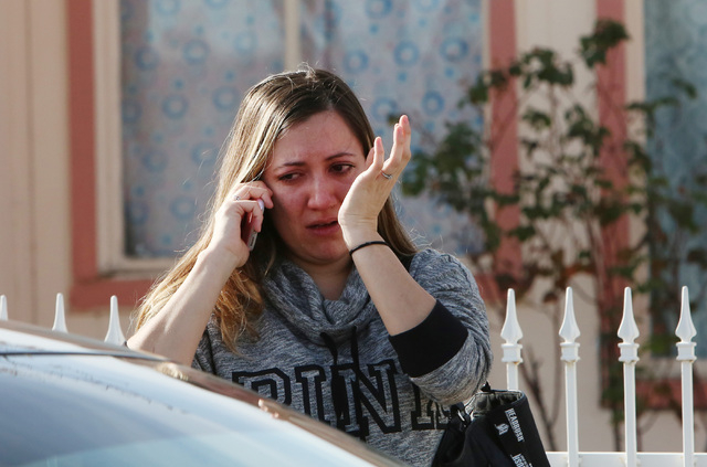 A woman whose mother's home was damaged in a fire reacts as she talks on the phone outside 1708 Pacific St., near the intersection of Oakey Boulevard and Eastern Avenue on Monday, Jan. 5, 2015. A  ...