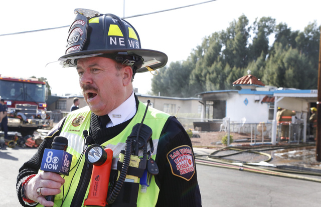 Las Vegas Fire Department PIO, Tim Szymanski addresses the media near a burned house at 1708 Pacific St., near the intersection of Oakey Boulevard and Eastern Avenue on Monday, Jan. 5, 2015. A per ...