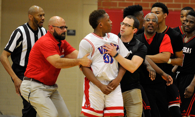 Valley's Darrion Daniels , center, is lead away after he was involved in a scuffle with Las Vegas late in the fourth quarter during a high school basketball game at Valley High School on Tuesday,  ...