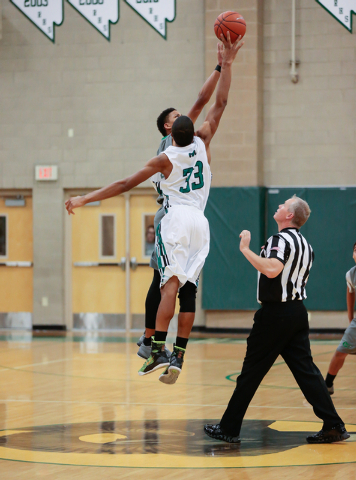 Rancho High School's Lamont Traylor (33) starts the game jumping against Green Valley High School's Isiah Macklin (35) during a basketball game with Green Valley High School (with a final score of ...