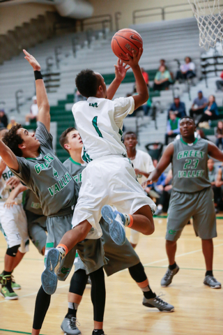 Rancho High School's David McKeever (1) leaps up and around Green Valley High School defender Xavier Jarvis (4), during a basketball game with Green Valley High School (with a final score of 57 to ...