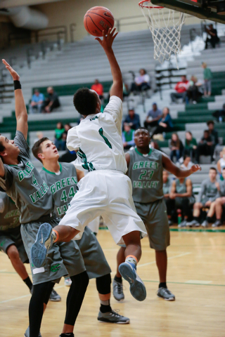 Rancho High School's David McKeever (1) leaps up and around Green Valley High School defender's, Xavier Jarvis (4) Canyon Lewis (44), during a basketball game with Green Valley High School (with a ...