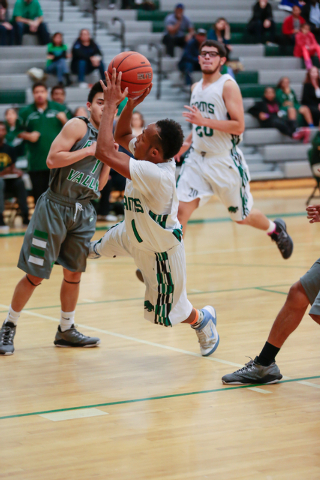Rancho High School's David McKeever (1) makes a shot at the basket while off balance and falling, during a basketball game with Green Valley High School (with a final score of 57 to 53 in favor of ...