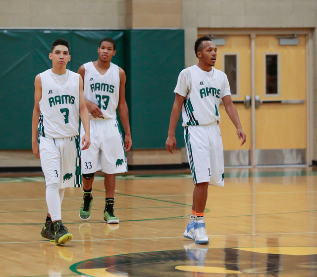 Rancho High School's Chrys Jackson (3) -left, Lamont Traylor (33) -center and David McKeever (1) walk back up court during a basketball game with Green Valley High School (with a final score of 57 ...