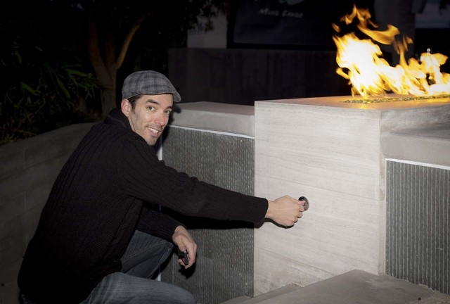 Jonathan Scott shows off the fire feature in the home's pool area. (Tonya Harvey/Real Estate Millions)