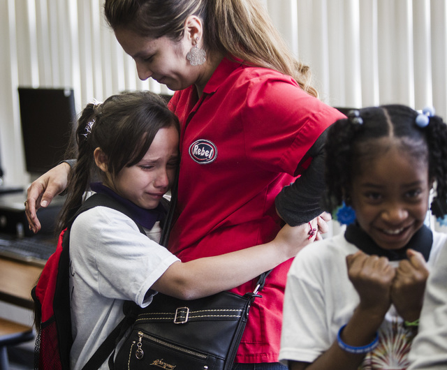 Daisy Ambriz, hugs  her daughter Brienna Morales, 8, after The Rogers Foundation awarded scholarships for students Wednesday, January 21, 2015 at Reynaldo Martinez Elementary School, 350 East Juds ...
