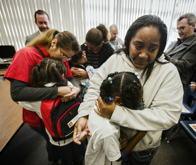 Amiela Akmal,right hugs her daughter Damya Sanders, 8, after The Rogers Foundation awarded scholarships for students Wednesday, January 21, 2015 at Reynaldo Martinez Elementary School, 350 East Ju ...