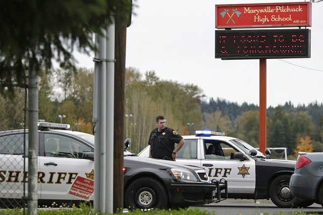 A Snohomish County deputy sheriff looks on at the entrance to Marysville-Pilchuck High School as police investigate a campus shooting in Marysville, Washington October 24, 2014. The school was hit ...
