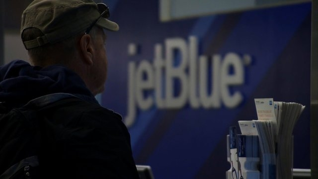 A passenger stands in line at a JetBlue Ticket Counter. (CNN)