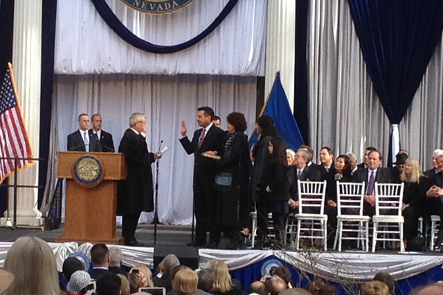 Gov. Brian Sandoval is sworn into office Monday, Jan. 5, 2015, by Chief Justice James Hardesty in a ceremony on the steps of the state Capitol. Next to the governor is his wife, First Lady Kathlee ...