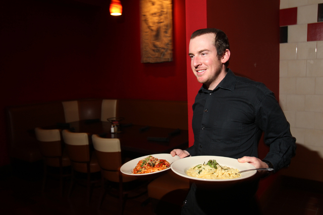 Server Erik Newkirk delivers dishes to a table during dinner service at Sauce restaurant, 721 Mall Ring Circle, in Henderson, Nev., Sunday, Dec. 28, 2014. (Erik Verduzco/Las Vegas Review-Journal)