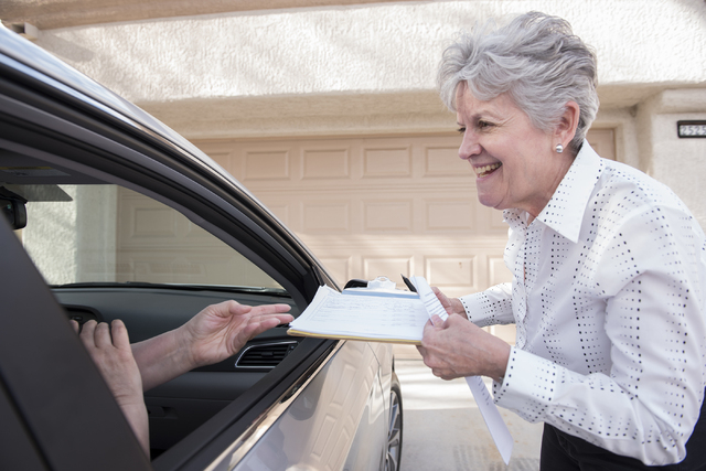 Volunteer Denise Denning instructs a Sun City Summerlin resident from out their vehicle on where to sign their signature for the initiative to halt the city's soccer stadium project in Las Vegas o ...