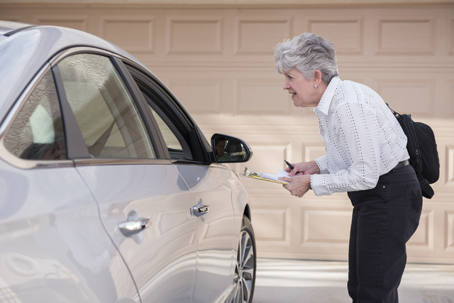 Volunteer Denise Denning explains to a Sun City Summerlin resident from out their vehicle about the signatures needed for the initiative to halt the city's soccer stadium project in Las Vegas on S ...