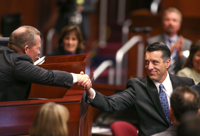 Lt. Gov. Mark Hutchison, left, shakes hands with Gov. Brian Sandoval following his State of the State address at the Legislative Building in Carson City, Nev., on Thursday night, Jan. 15, 2015. (L ...