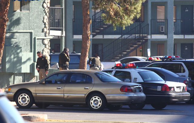 Las Vegas police officers are seen after a situation with a suicidal man armed with a knife is defused at an apartment complex at 3770 Swenson St. near Twain Avenue in Las Vegas on Thursday, Jan.  ...