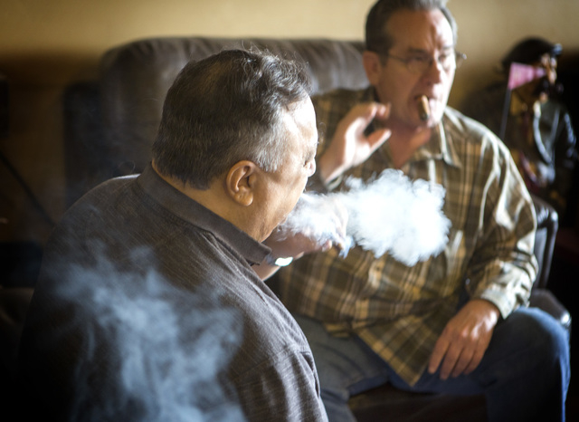 Customers Joe Fallico, left, and Dave Moretti  smoke cigars at En Fuego Cigars & Lounge, 328 West Sahara Avenue, on Wednesday, Jan. 28, 2015. Gov. Brian Sandoval is proposing to raise taxes on tob ...