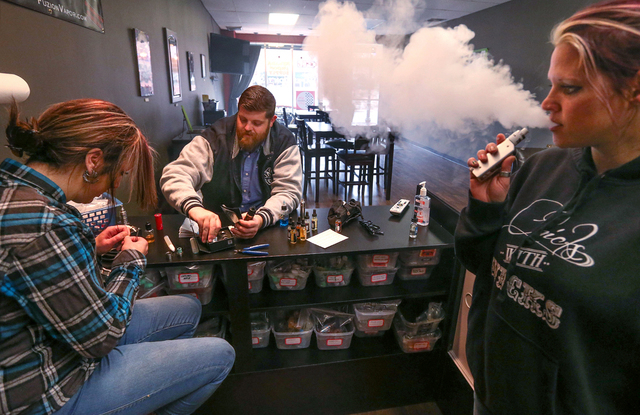 From left, Shelly McCurdy, Justin McClelland and Nina McIntosh smoke e-cigarettes at Nevada Vapor Supply in Carson City, Nev., on Tuesday, Jan. 27, 2015. Cigarette taxes and regulations on e-cigar ...