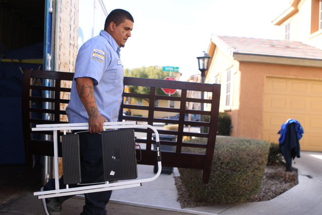 Carlos Fonseca, employee for Puliz Moving and Storage, moves furniture to a home inside the Tides community in Las Vegas Monday, Jan. 5, 2015. (Erik Verduzco/Las Vegas Review-Journal)
