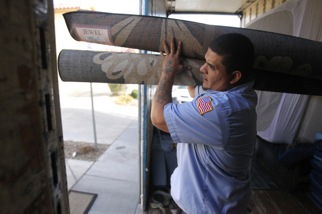 Carlos Fonseca, employee for Puliz Moving and Storage, moves carpets to a home inside the Tides community in Las Vegas Monday, Jan. 5, 2015. (Erik Verduzco/Las Vegas Review-Journal)