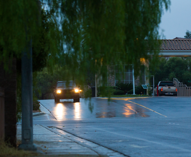 Vehicles enter and exit a gated community following an early morning rain at Katie Avenue and Grand Canyon Drive in Las Vegas on Tuesday, Jan. 27, 2015. (Chase Stevens/Las Vegas Review-Journal)