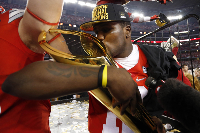 Ohio State Buckeyes quarterback Cardale Jones (12) kisses the national championship trophy after the 2015 CFP National Championship Game against the Oregon Ducks at AT&T Stadium on Jan. 12. (Matth ...
