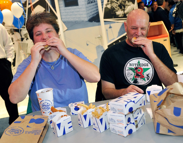 Linda Kitchel, left, and her friend Newman (no last name given) take their first bite of a White Castle burger during the grand opening of White Castle's newest and only location west of the Rocky ...