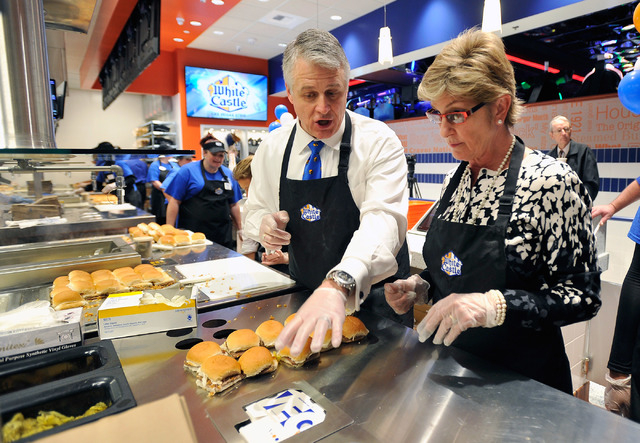 Dave Rife, left, White Castle's vice president & general manager, helps Clark County Commissioner Chris Giunchigliani prepare slider burgers at the grand opening of the hamburger chain's newest an ...